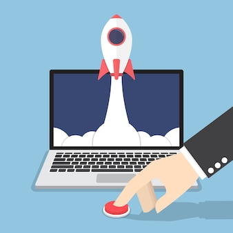 Biznesmen ręcznie naciskając przycisk, aby uruchomić rakietę z monitora laptopa