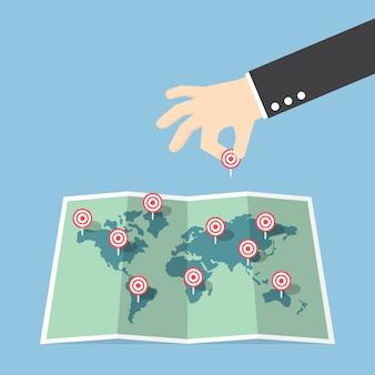 Biznesmen ręka pin cel do mapy świata