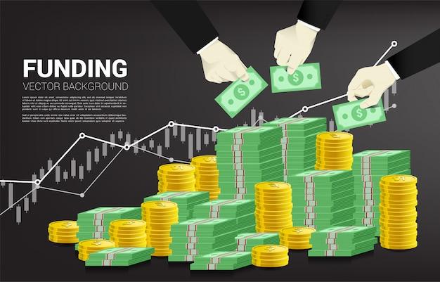 Biznesmen ręka umieścić pieniądze na stos pieniędzy.