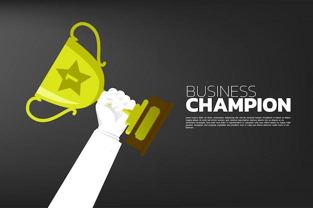 Biznesmen ręka z złocistą trofeum filiżanki nagrodą.