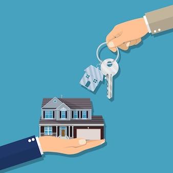 Biznesmen ręki daje kluczowi dla domu
