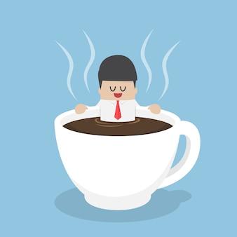 Biznesmen relaksuje w filiżance kawy
