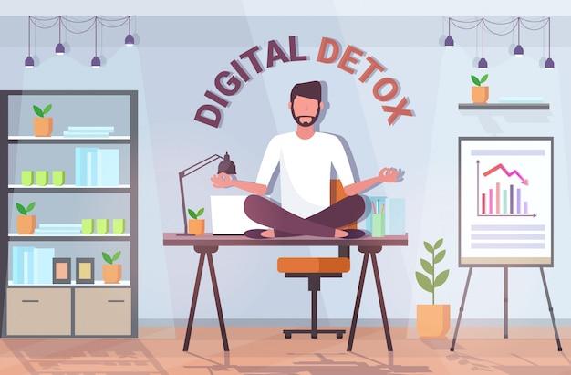 Biznesmen siedzi lotosu stanowią na stole pracy cyfrowy detoks pojęcie