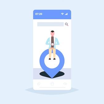 Biznesmen siedzi na geo pin tag wskaźnik mężczyzna trzymając telefon komórkowy za pomocą mobilnej nawigacji app lokalizacja znacznik gps pozycja koncepcja smartphone ekran pełnej długości