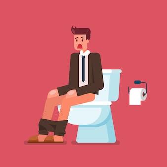 Biznesmen siedzi na muszli klozetowej i cierpi na biegunkę