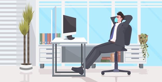 Biznesmen siedzi przy biurku w miejscu pracy dystans społeczny ochrona przed epidemią koronawirusa samoizolacja koncepcja pracy zdalnej biuro wnętrz poziome