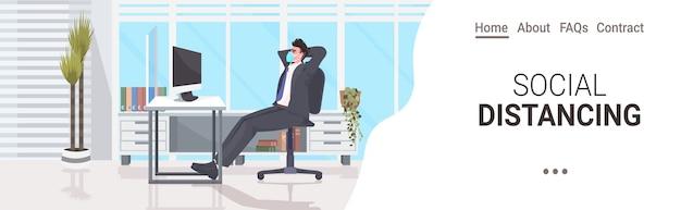 Biznesmen siedzi przy biurku w miejscu pracy dystans społeczny ochrona przed epidemią koronawirusa samoizolacja koncepcja pracy zdalnej wnętrze biura pozioma kopia przestrzeń