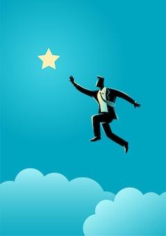 Biznesmen skacze, aby dotrzeć do gwiazdy