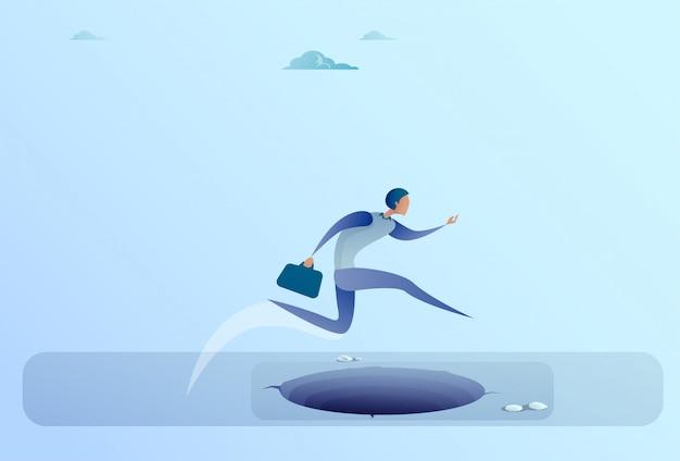 Biznesmen skok przez lukę do sukcesu business man koncepcja ryzyka