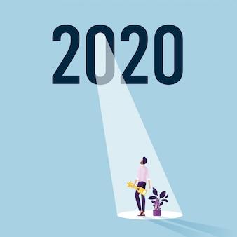Biznesmen stoi pod 2020 słowem nadzieja i sukces na nowy rok