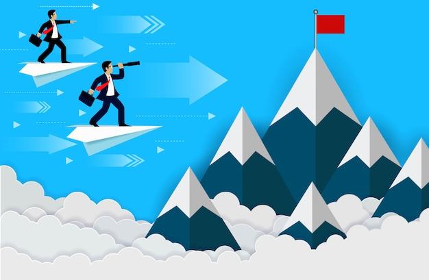 Biznesmen stojący na papierze samolotu patrząc z teleskopem na czerwoną flagę na szczycie wzgórza,