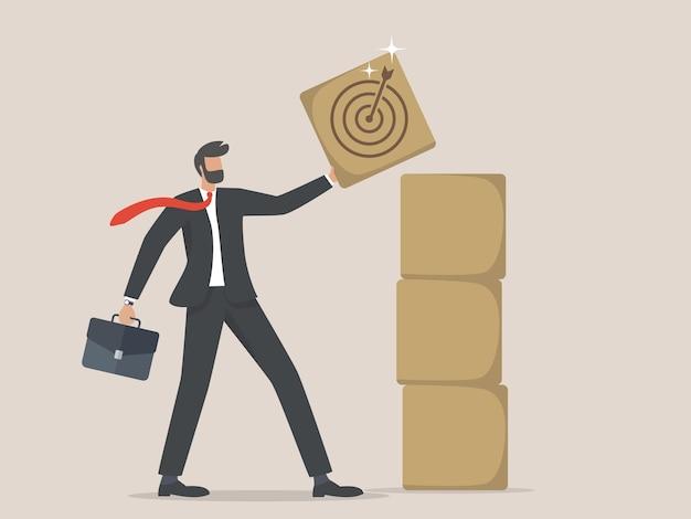 Biznesmen trzyma drewnianą kostkę ze znakiem celu