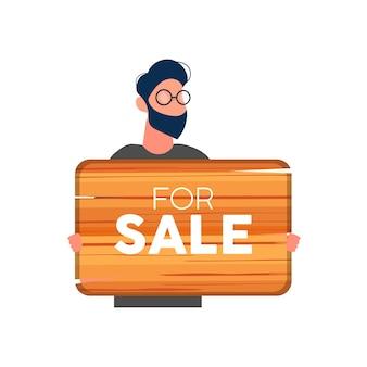 Biznesmen trzyma drewniany znak z napisem na sprzedaż. młody mężczyzna w garniturze trzyma drewniany znak na białym tle na białym tle. wektor.