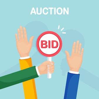 Biznesmen trzyma wiosło aukcji w ręku. licytacja, konkurencja aukcyjna. proces handlu biznesowego