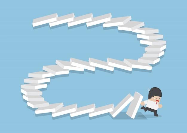 Biznesmen ucieka przed spadającymi domino