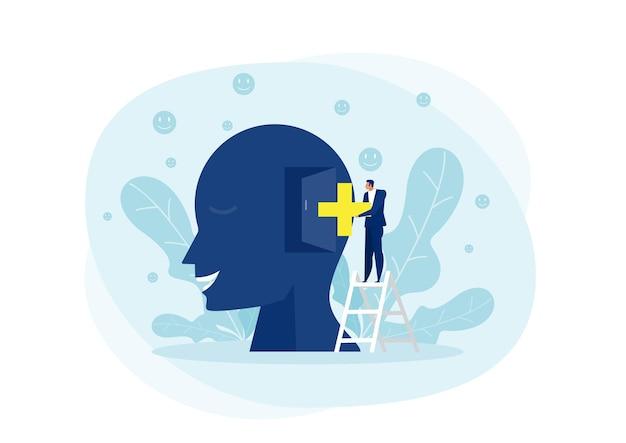Biznesmen umieścić znak pozytywnego myślenia na dużej głowie ludzkiej koncepcji.