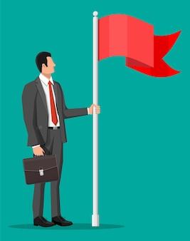 Biznesmen w garniturze z teczką stojący z czerwoną flagą.