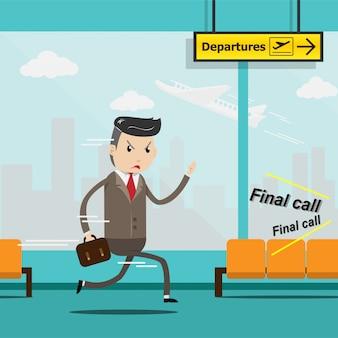 Biznesmen z bagażem biegnie w pośpiechu w terminalu lotniska