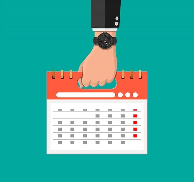 Biznesmen z kalendarza zegarka i spirali w ręku