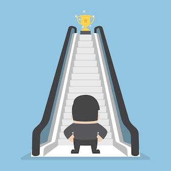 Biznesmen z ruchomymi schodami prowadzi trofeum