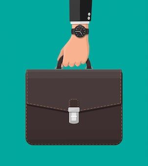 Biznesmen z zegarek na rękę i walizką w ręku