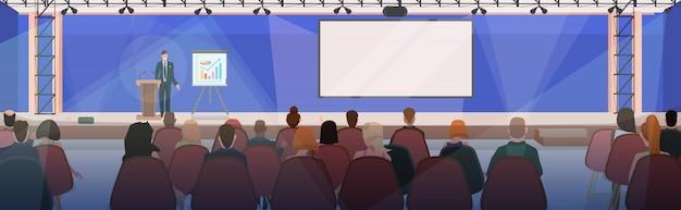 Biznesmeni na spotkaniu biznesowym z biznesmenem rozmawia z trybuny nowoczesnej sali konferencyjnej z wyżywieniem i tablicą typu flipchart sala konferencyjna wnętrze poziome mieszkanie
