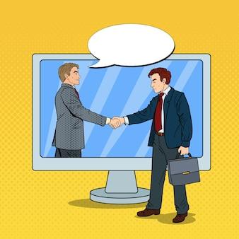 Biznesmeni pop-artu podają sobie ręce przez ekran komputera. umowa biznesowa.