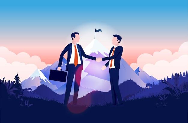 Biznesmeni, ściskając ręce przed szczytem góry
