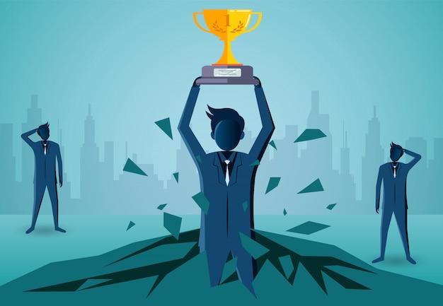 Biznesmeni stoi trzymający zwycięzcy trofeum nad jego głową rzucają z skały.