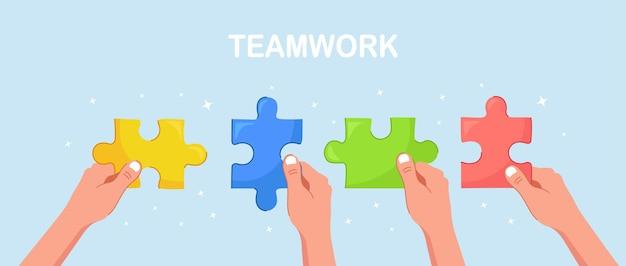 Biznesmeni trzymają w rękach kawałki puzzli i łączą je. metafora biznesowa pracy zespołowej. praca zespołowa, koncepcja sukcesu
