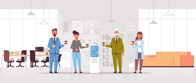 Biznesmeni współpracownicy rozmawiają i piją wodę, stojąc w pobliżu chłodniejszych pracowników po przerwie w nowoczesnym wnętrzu biurowym