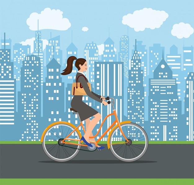 Biznesowa dama jedzie na krążownika rowerze.