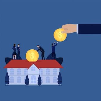 Biznesowa ręka daje monetę i umieszcza w domu hipoteczną metaforę inwestycji w nieruchomości.