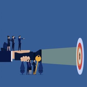 Biznesowa ręka trzyma latarkę do dziurki od klucza na metaforze celu wyraźnego.