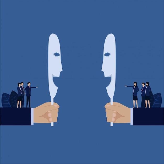 Biznesowa ręka trzyma uśmiechniętą maskę, podczas gdy za zespołem obwinia się nawzajem metaforę hipokryta.