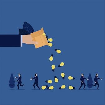 Biznesowa ręka wylewa pudełko i pomysły spadają na zespół biznesmenów.