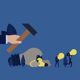 Biznesowy chwyt trzymający młot uderzony w żarówkę zepsutego pomysłu przynosi małą metaforę żarówki pomysłu dużego i małego pomysłu.