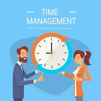 Biznesowy mężczyzna i kobieta z zegarowym czasu zarządzania pojęciem