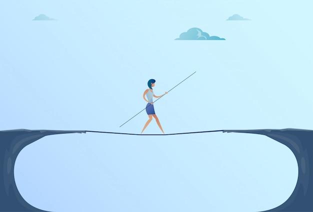 Bizneswoman chodzić nad cliff gap mountain business woman równoważenie drewniany kij most