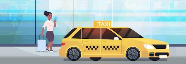 Bizneswoman używa mobilną app rozkazuje taxi na ulicznej biznesowej kobiecie w formalnej odzieży z bagażem blisko żółtego taksówki miasta transportu usługa pojęcia pełnej długości horyzontalnej
