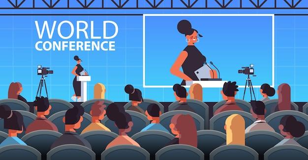 Bizneswoman wygłasza przemówienie na trybunie z mikrofonem na korporacyjnej międzynarodowej konferencji światowej ilustracja wnętrze sali wykładowej