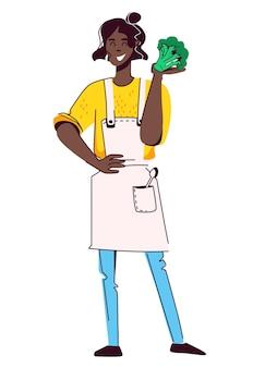 Blcak dziewczyna w żółtym swetrze i białym fartuchu z warzywami koncepcja zdrowego gotowania żywności