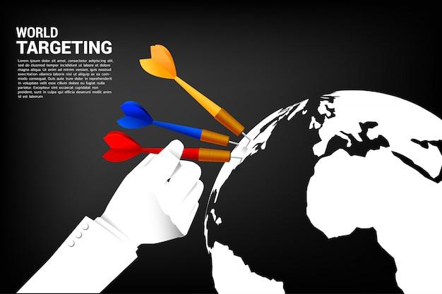 Bliska ręka trzymać strzałkę dart hit na świecie.