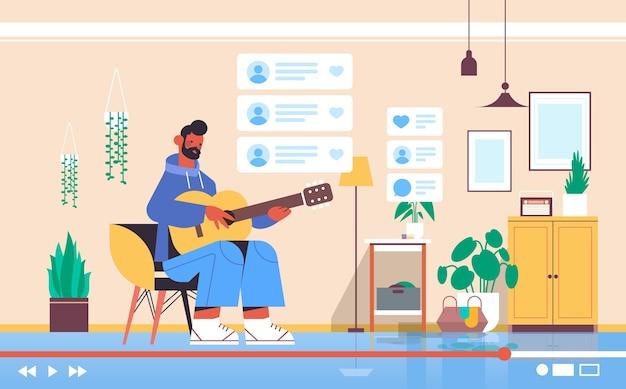 Bloger mężczyzna grający na gitarze nagrywanie na gitarze blog wideo na żywo strumieniowanie na żywo koncepcja blogowania wnętrze salonu w poziomie