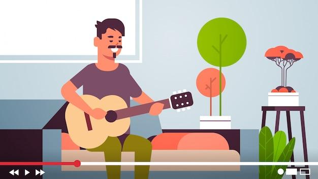 Bloger muzyczny nagrywający strumień wideo online dla vloga męski vloger gra na gitarze blogowanie koncepcja nowoczesny salon wnętrze poziome