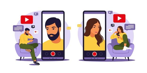 Blogerzy wideo kobiety i mężczyzny siedzą na kanapie z telefonem i nagrywają wideo za pomocą smartfona. różne media społecznościowe. ilustracja w stylu płaski.