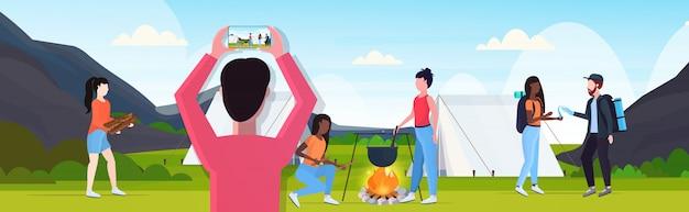 Blogger podróży fotografowanie podróżników camper ludzi na smartfonie aparat blogowanie camping koncepcja krajobraz tło poziome