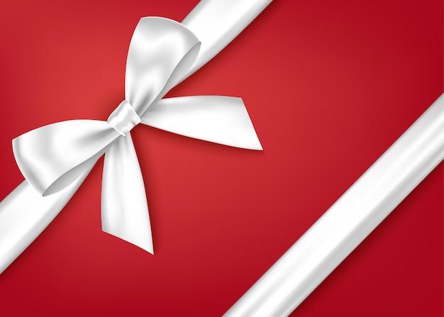 Błyszcząca biała ozdobna wstążka prezentowa i kokardka do dekoracji narożnika.