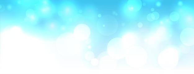 Błyszczące światła bokeh na niebie w kolorze niebieskim tle