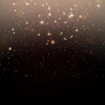 Błyszczące złote cząsteczki musujące gwiezdny pył na ciemnym tle.
